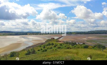 Looking across the causeway from Cramond Island to Cramond in Edinburgh with fluffy white clouds in blue sky - Stock Photo