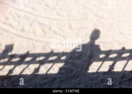 Shadow of person looking over a fence  at a sandy beach. - Stock Photo