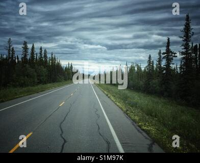 Straight road  with vanishing point leading into remote wildness of the Alaska interior on cloudy day. - Stock Photo