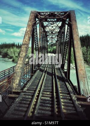 Train tracks leading across metal railway bridge to trees on distance shore. Steel railway bridge between Fairbanks - Stock Photo