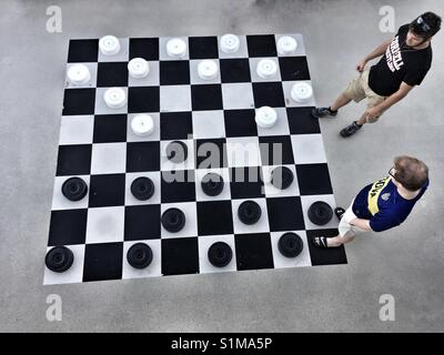 Looking down at two males playing a game of checkers on a giant outdoors checker board on cruise ship - Stock Photo