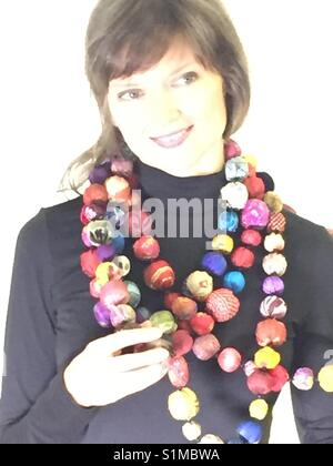 Beautiful young woman showing off her new fabric necklace. - Stock Photo