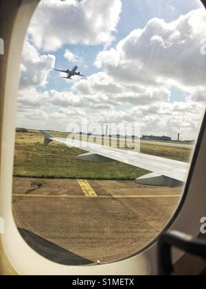 View from aircraft window showing another aircraft taking off. - Stock Photo