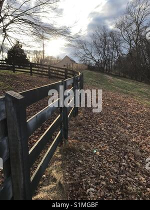 Beautiful shot of the sun going down on a hilltop farm in Tennessee. The weathered fence and fallen leaves come - Stock Photo