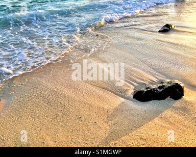 Stones washed up on a beach with surf rolling in at sunset . Hawaii - Stock Photo
