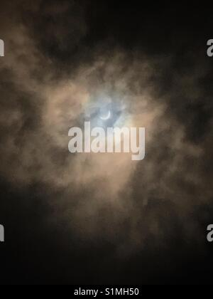 Solar eclipse visible through hazy dark clouds , Jacksonville, Florida, August 21, 2017 - Stock Photo
