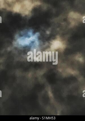 Solar eclipse visible through hazy dark clouds, Jacksonville, Florida, August 21, 2017 - Stock Photo