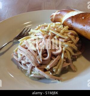 Homemade salad made of stripes of sausages, cheese on white plate and Bavarian pretzel. Swiss sausage salad. - Stock Photo