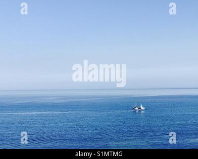 Looe Cornwall fishing boat on a blue sea under a blue Sky - Stock Photo