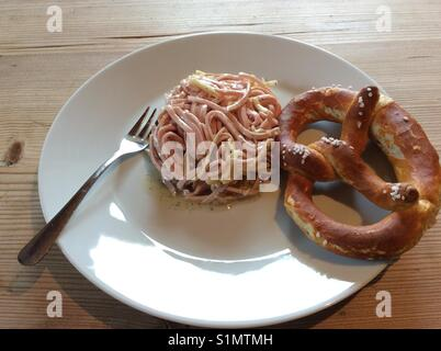 Swiss sausage salad and Bavarian pretzel on white plate - Stock Photo
