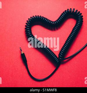 A coiled headphone cable made into a heart shape on a red background - Stock Photo
