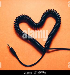 A coiled headphone cable made in to a heart shape on a orange background - Stock Photo