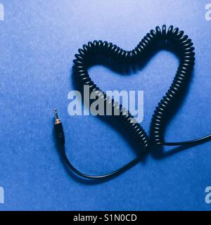 A coiled headphone cable made into a heart shape on a blue background - Stock Photo