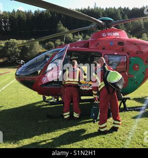 The crew in the process of boarding a Wales Air Ambulance - Stock Photo