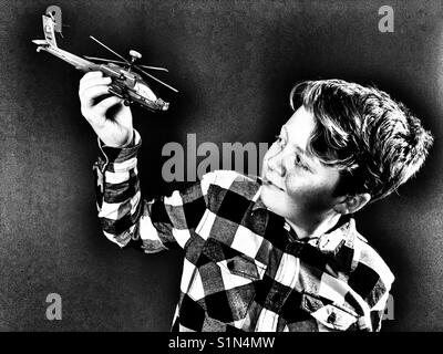Boy playing with toy helicopter - Stock Photo