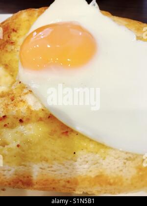 Fried egg on hot white buttered toast - Stock Photo