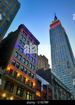 New York City at dusk with the brightly lit Ditson building and Empire State building, midtown Manhattan, USAA - Stock Photo