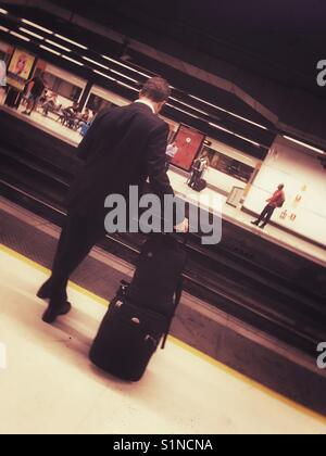 Business traveller waiting for a train - Stock Photo