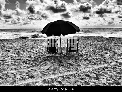 Two beach chairs and an umbrella in black and white - Stock Photo