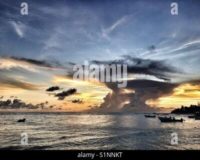 Sun setting behind a dissipating cumulonimbus cloud in St. Laurence Gap, West coast of Barbados - Stock Photo