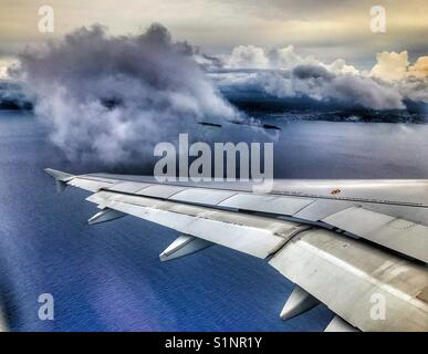 View from plane of clouds and ocean. - Stock Photo
