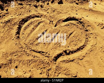 Heart drawn in red sand on Xi beach on Kefalonia - Stock Photo