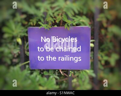 No bicycles to be chained to the railing sign. - Stock Photo