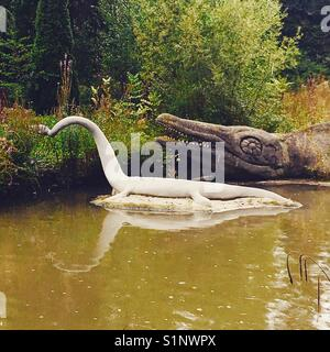Stone dinosaurs in Crystal Palace - Stock Photo