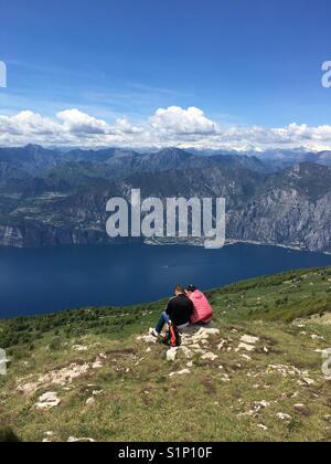 A couple on holiday sitting on a rock on Mount Baldo overlooking Lake Garda, Italy - Stock Photo