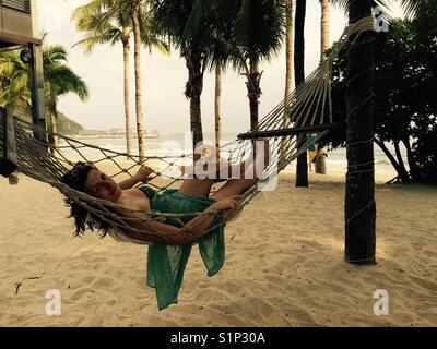 A girl in a hammock on a sandy beach with palm trees - Stock Photo