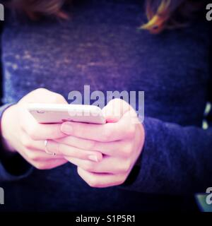 A mid section shot of a young girl holding her mobile phone in her hands whilst texting in a close-up - Stock Photo