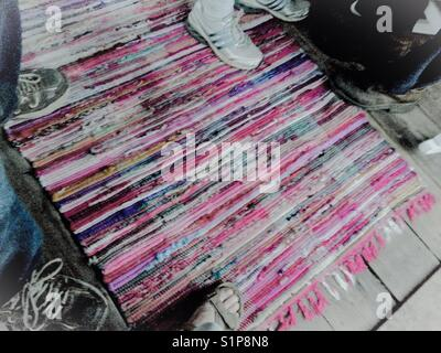 The social rug- feet meet on the rug - Stock Photo