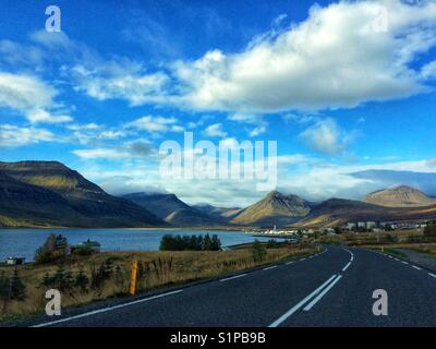Mountain view from the car. On the road, driving through a small town in Iceland - Stock Photo