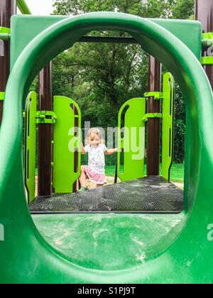 Toddler girl climbing on green playground at park - Stock Photo