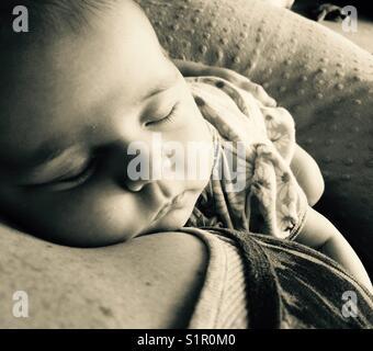 Newborn baby girl sleeping on mother's shoulder - Stock Photo