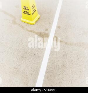 Wet floor caution cone on pool deck - Stock Photo