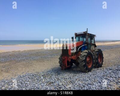 Tractor on beach during the summer - Stock Photo