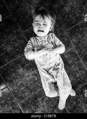 Black and white image of toddler crying on a tile floor - Stock Photo