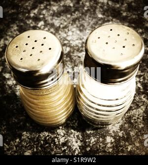 Close up of salt and pepper shakers on a restaurant table - Stock Photo