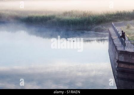 The fisherman fishing in a foggy summers morning. - Stock Photo