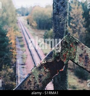 Train tracks towards Chernobyl power plant, framed by rusting and peeling metal railings - Stock Photo