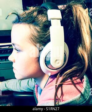 Profile view of girl wearing large white headphones - Stock Photo