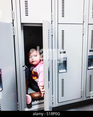 Little girl wearing pink Batman sweater and rain boots sitting in a locker room locker - Stock Photo
