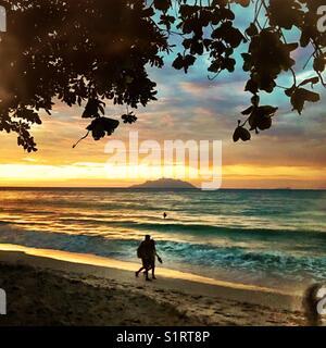 People on Seychelles beach Beau Vallon sunset - Stock Photo