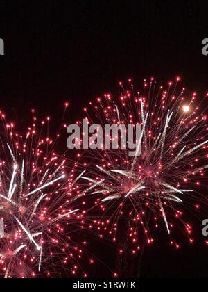 Detail image of two exploding fireworks that contain the colour red and the tone white. Light trails are evidence - Stock Photo