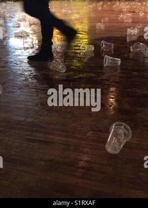 Empty plastic beer glasses and spilt beer on floor at the end of a concert - Stock Photo