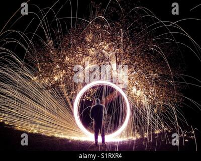 Steel wool spinning under apple tree - Stock Photo