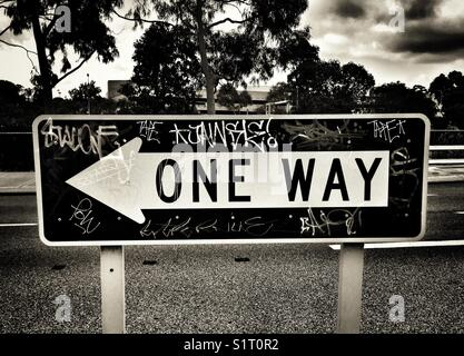 One Way Street sign with graffiti on. - Stock Photo