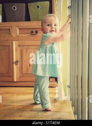 Baby girl cruising along safety gate - Stock Photo