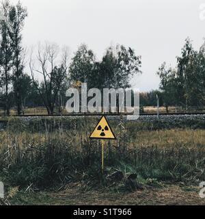 A radioactive sign on a field in Pripyat City, Chernobyl, Ukraine - Stock Photo